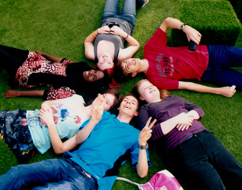 Circle of IB students laying on the grass